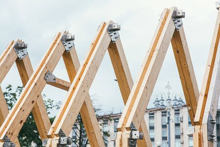 Wooden rafters of unfinished roof against the background of the city and white sky. The concept of building and creating new housing