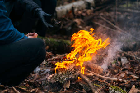 Man warms his hands on fire. Burning wood at evening in the forest. Campfire at touristic camp at nature. Barbeque and cooking outdoor fresh air. Flame and fire sparks on dark abstract background. Concept of safety and responsibility to nature. Banque d'images