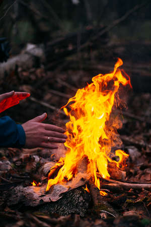 Man warms his hands on fire. Burning wood at evening in forest. Campfire at touristic camp at nature. Barbeque and cooking outdoor fresh air. Concept of safety and responsibility to nature Banque d'images