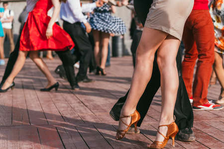 people are dancing outdoors in the park at sunny day. beautiful female feet in dancing shoes in the foreground and background and red skirt