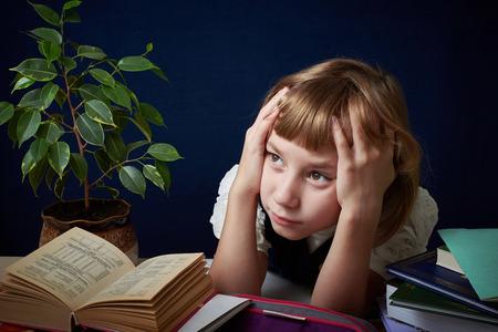 confundido: Colegiala cansado de hacer difícil la tarea. Ella quiere jugar con sus amigos en el patio, pero que necesita para hacer su tarea.