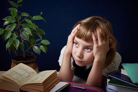confused: Schoolgirl tired of doing difficult homework. She wants to play with her friends in the yard, but you need to do your homework. Stock Photo