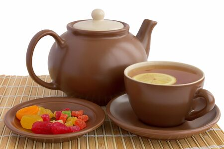 Ceramic teacup with teapot and candied fruits Stock Photo