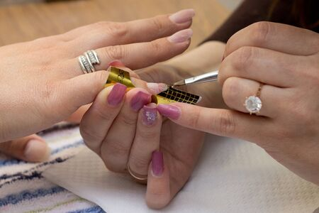 Applying gel during professional manicure using pattern photo