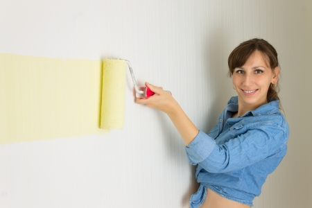 Happy smiling woman painting the wall with roller Stock Photo - 14874137