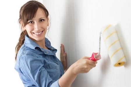 painting wall: Mujer sonriente feliz que pinta la pared con el rodillo Foto de archivo