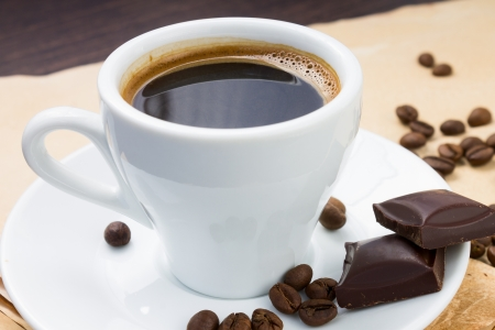 Cup of coffee and beans with chocolate on paper background photo