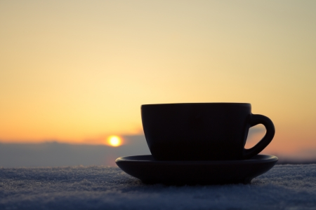 coffee time: Romantic winter evening  Cup of coffee or tea in rays of sunset