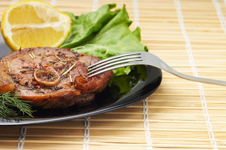 Grilled steak with salad and lemon on black plate with fork  Bamboo background