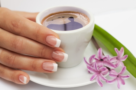 Beautiful manicured hand with french nails and cup of coffee and flowers at saucer on white background