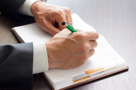 Businessman makes notes to his work diary