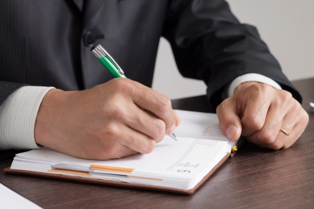 Businessman makes notes to his work diary photo