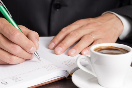 Businessman notes his idea to diary at workplace with cup of coffee photo