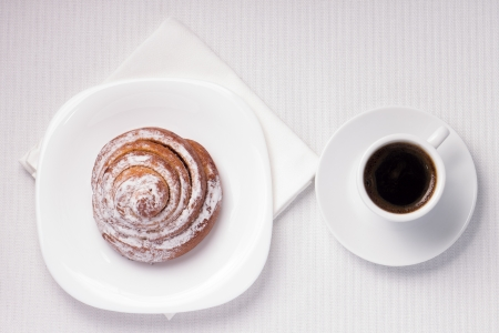 Top View Cup of Black Coffee with a Sweet Bun on White Tablecloth photo
