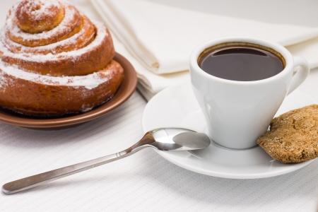 Tasse schwarzen Kaffee auf weiße Platte mit einem süßen Brötchen und Plätzchen Rye