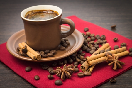 Cup of Coffee with Beans and Spices on Red Napkin
