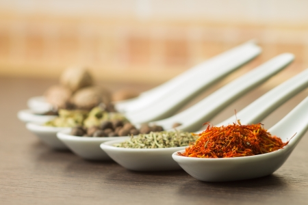 Various of Spice in Ceramic Spoon on Wood background