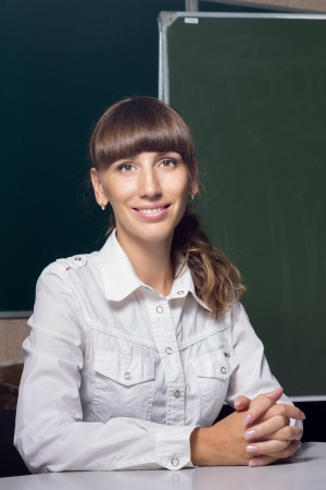 Young attractive teacher or coach at the table near blackboard photo