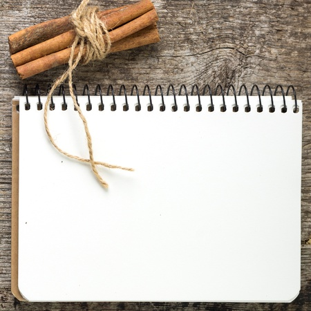Blank Recipe book with bunch of cinnamon on old wood board photo