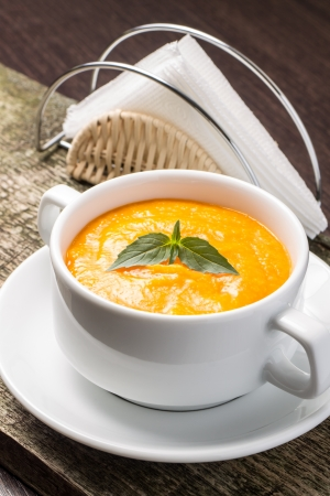 Pumpkin soup in white bowl with fresh basil photo