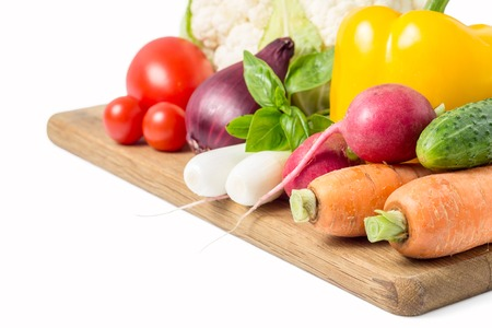 Fresh vegetables at wood cutting board isolated on white photo