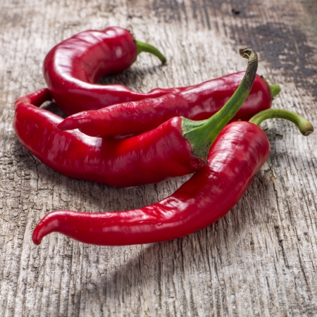 Red chili pepper on weathered wooden background Stock Photo