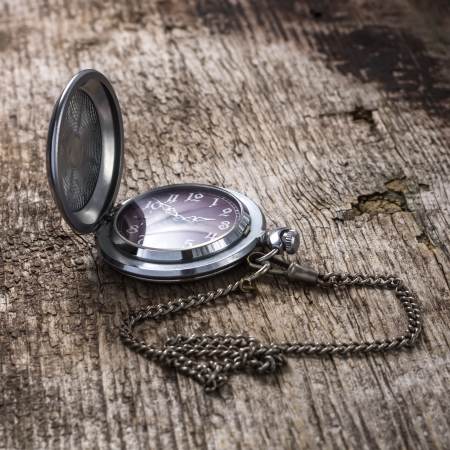 Old pocket watch at weathered wood plank