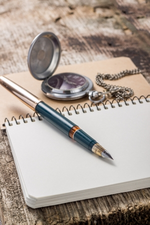 Golden in pen with pocket watch at white notebook