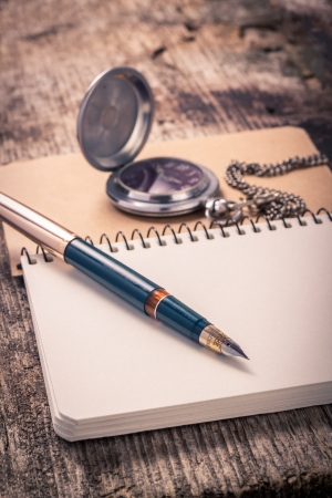 Vintage ink pen and pocket watch on notebook Stock Photo