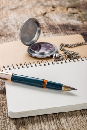 Golden in pen with pocket watch at white notebook photo