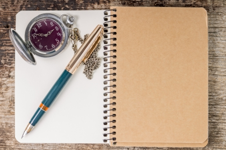 Top view of notebook with ink pen and pocket watch photo