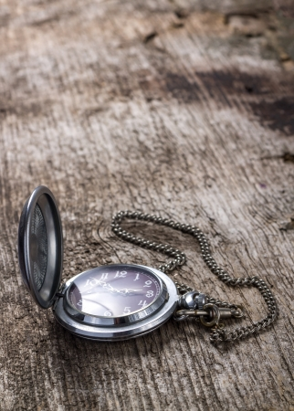 Old pocket watch on wood background with copyspace photo