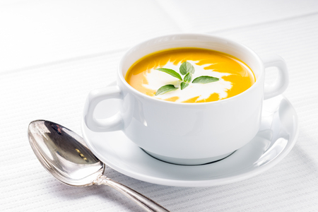Pumpkin soup  with basil on served table Stock Photo