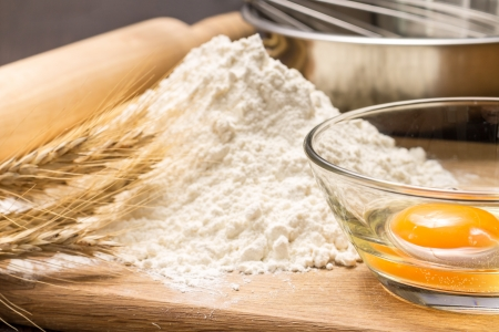 Baking ingredients with wheat ears on wood board Stock Photo