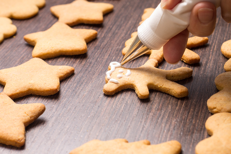 Decorating of gingerbread bears on wooden table photo