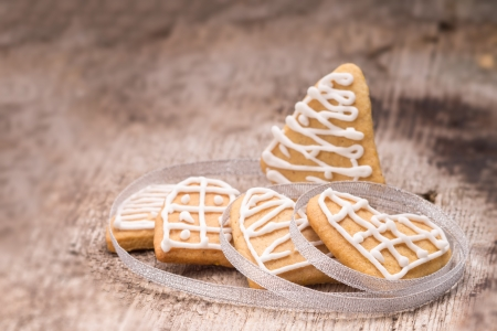 Christmas decoration. Gingerbread cookies on wood background. Selective focus photo