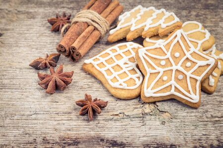 Gingerbread cookies with spices on wooden background. photo