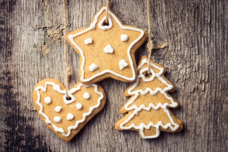 Gingerbread cookies hanging over wooden background. Christmas decoration photo