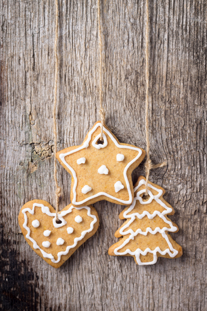 Christmas decoration. Gingerbread Cookies Hanging over wooden background photo