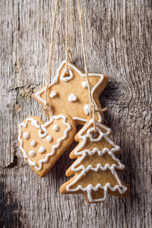 gingerbread cookies: Christmas decoration. Gingerbread Cookies Hanging over wooden background
