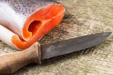Fresh Salmon on rustic weathered wooden board with knife