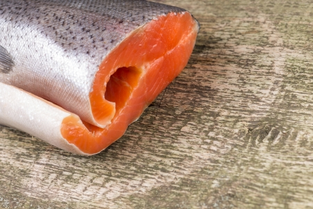 Fresh Salmon on rustic weathered wooden board photo
