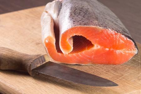 Fresh Salmon with knife on cutting board Stock Photo