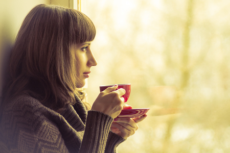 Coffee. Pretty Girl drinking Coffee or Tea near Window. Warm colors toned Stock Photo
