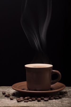 Coffee with Light Steam and Coffee Beans on Black Background Stock Photo