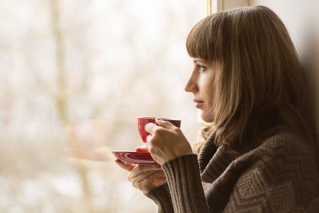 Schöne Mädchen trinken Kaffee oder Tee in der Nähe von Fenster