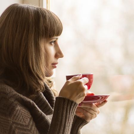 Young Pretty Woman Drinking Coffee or Tea near Window in Cafe Stock Photo