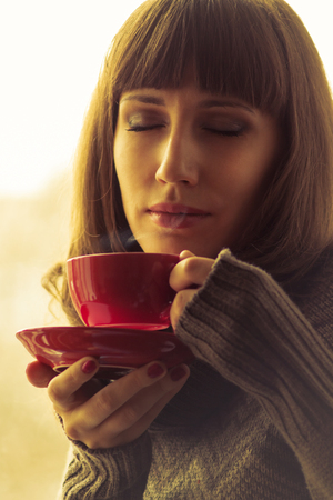 Young Beautiful Woman Drinking Coffee or Tea  with Steam. Warm color toned photo