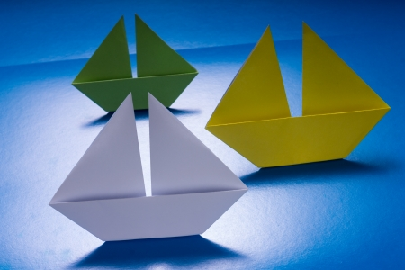 Group of Paper Boats Sailing on Blue paper sea  Origami Ship photo