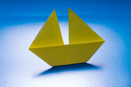 Paper Yellow Boat Sailing on Blue paper sea  Origami Ship Stock Photo